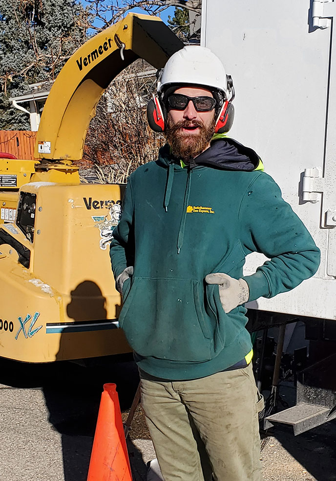 Blake Hepburn in front of tree-cutting equipment